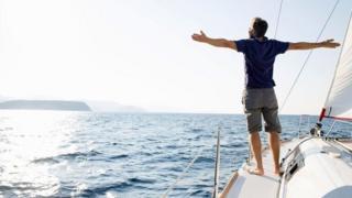 شاب يقف على متن قاربه الخاص وسط البحر
