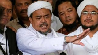 นายรีซีค (กลาง) เป็นผู้นำกลุ่มแนวร่วมผู้ปกป้องอิสลาม ซึ่งเป็นกลุ่มมุสลิมสุดโต่ง