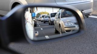 Traffic seen in rear-view mirror