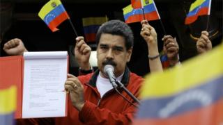 Venezuela's President Nicolas Maduro shows a document with the details of a constituent assembly to reform the constitution during a rally at Miraflores Palace in Caracas, Venezuela May 23, 2017.