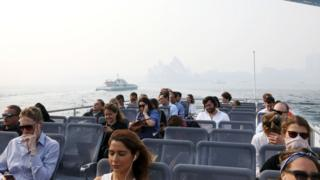 Passengers on a ferry on Sydney Harbour during a smoke haze across the city which has almost obscured the Sydney Opera House in the background