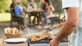 Generic image of a man cooking meat on a barbecue with his family seated at a table in the background