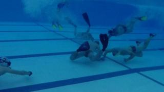 Underwater hockey players in the pool