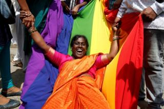 An activist of the LGBT community celebrates after the Supreme Court's verdict