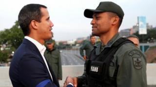 خوآن گوایدو در حال دست دادن با یک سرباز