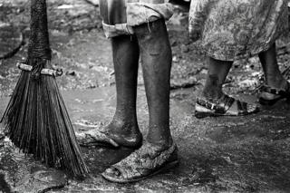 A close up of the legs of sanitation workers with a broom