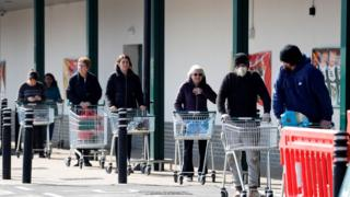 "Shoppers observe social distancing as they wait in a queue outside a supermarket in Fleet, Hampshire on March 28, 2020. - The two men leading Britain""s fight against the coronavirus - Prime Minister Boris Johnson and his Health Secretary Matt Hancock - both announced Friday they had tested positive for COVID-19, as infection rates accelerated and daily death rate rose sharply."