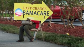 A woman holds an Obamacare sign in front of a medical centre in Miami in November 2017