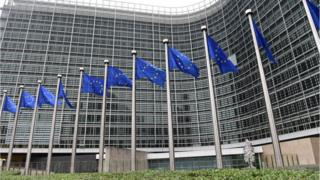 European Commission headquarters, HQ / Berlaymont building, with European Union flags, Brussels.