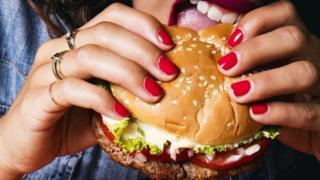 Mujer mordiendo una hamburguesa