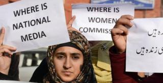 Activists holding placards during a protest in Srinagar over the rape and murder of a child.