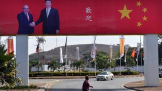 A woman crosses a street with a billboard on which the Prime Minister of Papua New Guinea, Peter O. Neill (above L), shakes hands with Chinese President Xi Jinping, and the message
