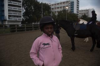 A small girl stands in a riding hat