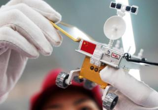 An employee inspects a 1:8 scale model of the Chang'e-4 lunar probe at a production line