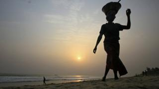 A woman walks along a beach at sunset in Grand Bassam, Ivory Coast, 27 January 2018
