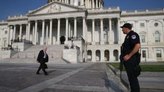 Sen Michael Enzi (R-WY) walks past a US Capitol Police officer standing guard in front of the US Capitol Building, on June 14, 2017 in Washington, DC.