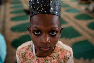 A young boy looks on during a special Jumu'ah prayer service at the Central Mosque in Lagos, Nigeria. He is wearing a hat and his eyes are lined in kohl - Friday 15 February 2019