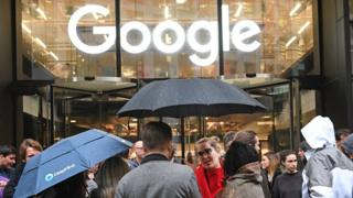 People standing with umbrellas outside Google office