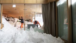 Workers clear snow from the Säntis hotel after an avalanche hit it in Schwägalp, Switzerland
