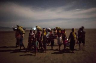 Un grupo de refugiados camina en la noche tras cruzar el río Naf, en su escape de la brutalidad del ejército de Birmania.