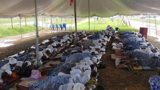 Women lie down inside tent.