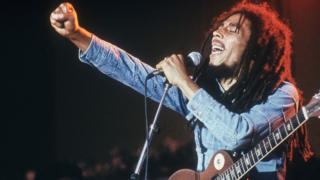 Bob Marley levantando el brazo en medio de un concierto