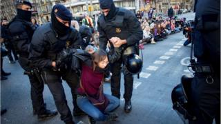 Officers of Mossos d'Esquadra, the Catalan regional police, remove women who block the Gran Via avenue during a sit-in protest in Barcelona