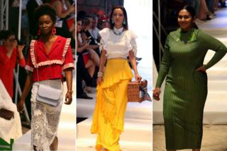 Three models are pictured walking down a catwalk. The first wears a red top and white skirt, the second has a white top and yellow top. The third model wears a green dress.
