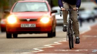 man cycling in front of car