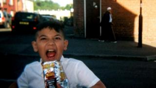 Young boy with bag of crisps, old man in background