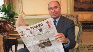 French industrialist and politician poses with a copy of French newspaper Le Figaro in Paris on 5 February 2002.
