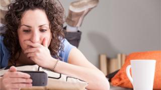 Mujer con expresión de sorpresa mirando el teléfono
