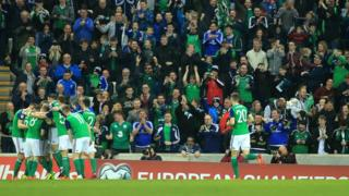 Northern Ireland's soccer players and supporters celebrate after Northern Ireland scored their first goal against Norway's with in minutes of kick off during the FIFA World Cup 2018 group C qualifying soccer match between Northern Ireland and Norway at the National Football Stadium at Windsor Park, Belfast, Britain,