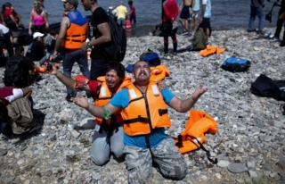 Refugees from Syria pray after arriving on the shores of the Greek island of Lesbos