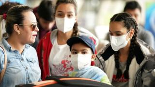 A family at Dulles International Airport a day after US President Donald Trump announced travel restrictions on flights from Europe to the US for 30 days to try to contain the coronavirus in Virginia, US, on 12 March 2020