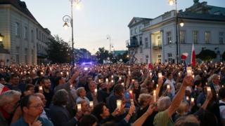 Protesters hold candles in front of the Presidential Palace in Warsaw, Poland, 18 July 2017