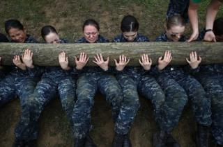 Recruits perform push ups with a twelve foot log on top of them during the annual Sea Trials