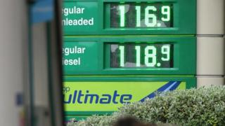 The price of petrol and diesel fuels are shown on an electronic display board outside a BP petrol station in Manchester, north-west England on October 18, 2016