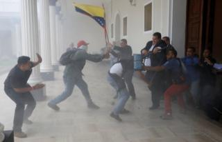 国旗を掲げながら国会に乱入する群衆(5日、カラカス)