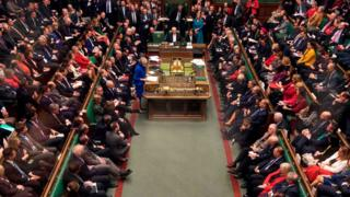 A handout photograph released by the UK Parliament shows Britain's Prime Minister Theresa May (centre left) as she speaks in the House of Commons