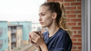 A woman drinks coffee in a new home