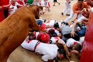 A wild cow leaps over revellers as it enters the bullring following the seventh running of the bulls at the San Fermin festival in Pamplona, northern Spain