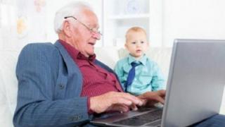 رجل كبير يستخدم كمبيوتر محمول وبجانبه طفل صغير