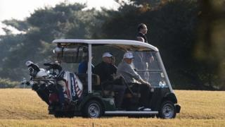 Donald Trump (front R) and Japanese Prime Minister Shinzo Abe (front L) return in a golf cart after playing a round of golf