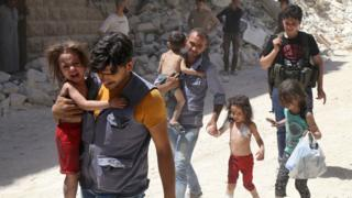 Syrian men carry injured children amid the rubble of destroyed buildings following reported air strikes on the rebel-held neighbourhood of Al-Mashhad in the northern city of Aleppo, on July 25, 2016