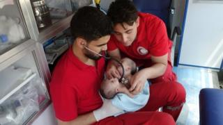 Red Crescent workers examine the babies