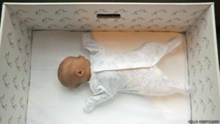 Un bebé duerme en una caja de cartón.