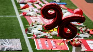Tributes are placed on the pitch before a memorial service to mark the 27th anniversary of the Hillsborough disaster, at Anfield stadium on April 15, 2016 in Liverpool, England.