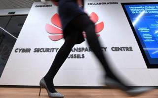A woman walks past a logo at the entrance of the European Huawei Cyber Security Transparency Centre during its opening in Brussels on March 5, 2019.