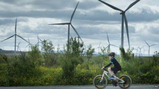 Boy cycling against a backdrop of a wind farm